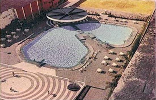 Vista aérea do conjunto de piscinas,  vestiários com chuveiros quentes e frios e hall para troca de roupas, e bar  em condição de atender inclusive com pequenos almoços (1975)